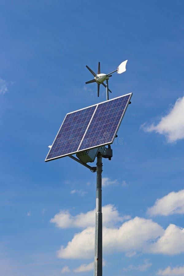 Windgenerator en zonnepaneel op een blauwe hemel Photovoltaic cellen Methode om alternatieve energie te verkrijgen Schoon ecologi stock foto