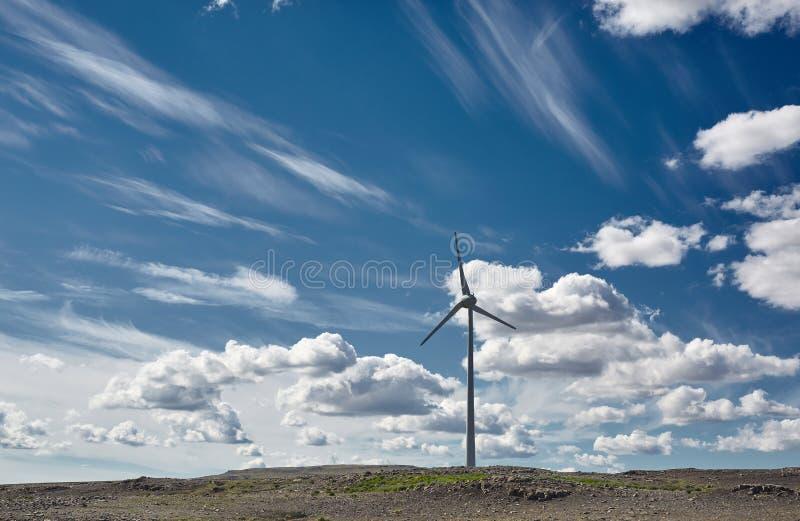 Windgenerator tegen de blauwe hemel met witte wolken stock foto's