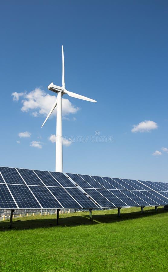 Windgenerator van elektriciteit van drie bladen en zonnepanelen van een batterij van groene gras van de fotocellen het blauwe hem stock foto's