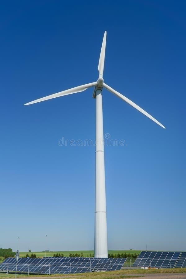 Windgeneratorturbine und Sonnenkollektoren einer Batterie auf blauem Himmel, alternative Energiequellen stockbilder