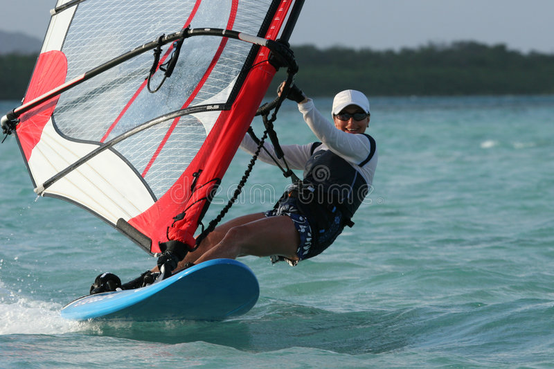 A windgirl. A young woman sweeping over a blue lagoon on a windsurfer royalty free stock photo