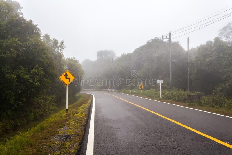 Windiger Waldweg mit einem Kurvenzeichen an einem nebeligen Tag an Nationalpark Doi Inthanon stockbild