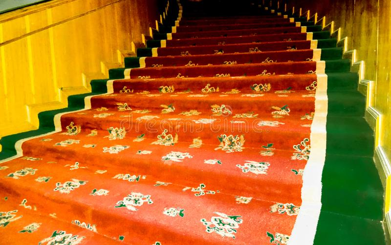 Winding colored carpeted stairs with wood. Carpeted winding stair curling to the left with wooden walls royalty free stock images