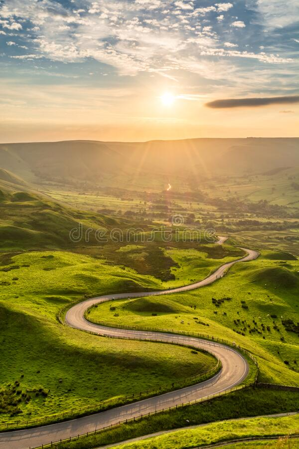 Winding country road leading to Edale in the English Peak District with beautiful golden light shining through valley. stock photos