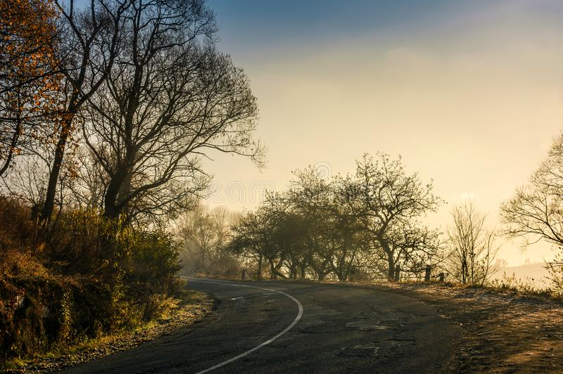 Winding countryside road in late autumn fog stock photos