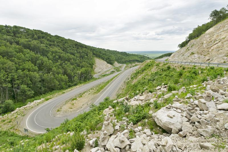 Winding and dangerous mountain road serpentine going on a steep slope in the mountains stock image