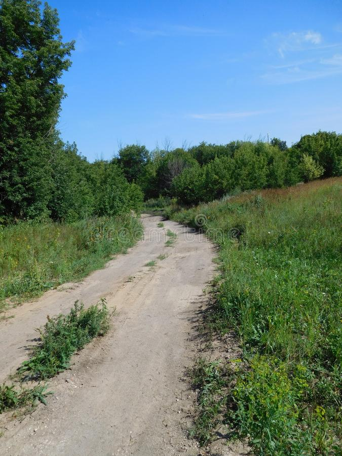 Winding dirt path in a field stock image