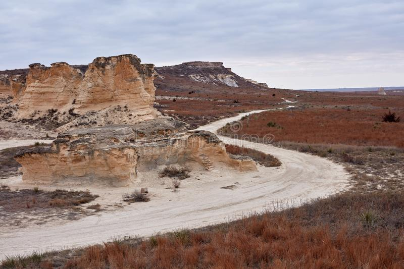 Winding dirt road through Castle Rock Badlands. Kansas with eroded limestone pillar formations in a dry barren landscape royalty free stock photo