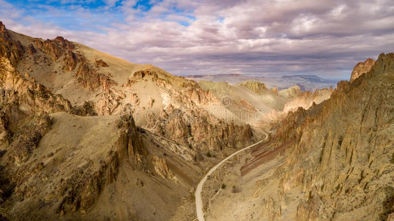 Winding dirt road heads to the Owyhee reservoir in Oregon. Unique view of a canyon in Oregon with a road in the bottom of it royalty free stock photos