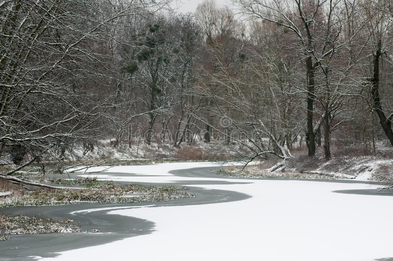 Winding frozen river with snow on the ice royalty free stock photo