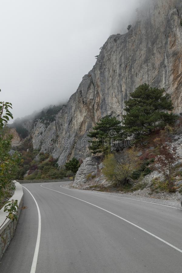 Winding mountain road on cloudy day. Winding mountain road in fog on cloudy day stock image