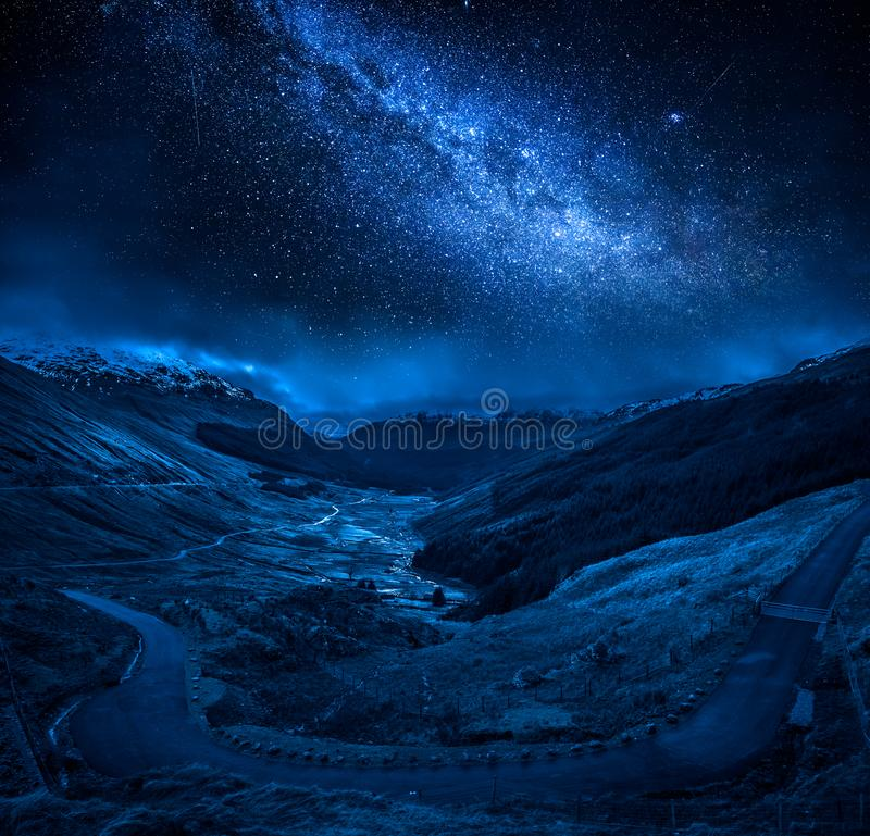 Winding mountain road over a canyon at night with stars stock image