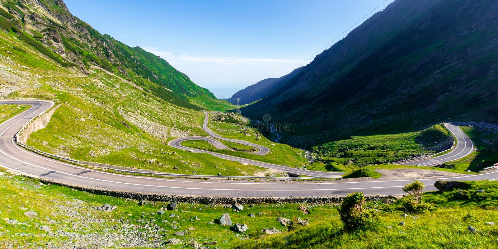 Winding mountain road on a sunny day. Empty highway run through valley. open vista in the distance. great european journey in summertime concept royalty free stock image