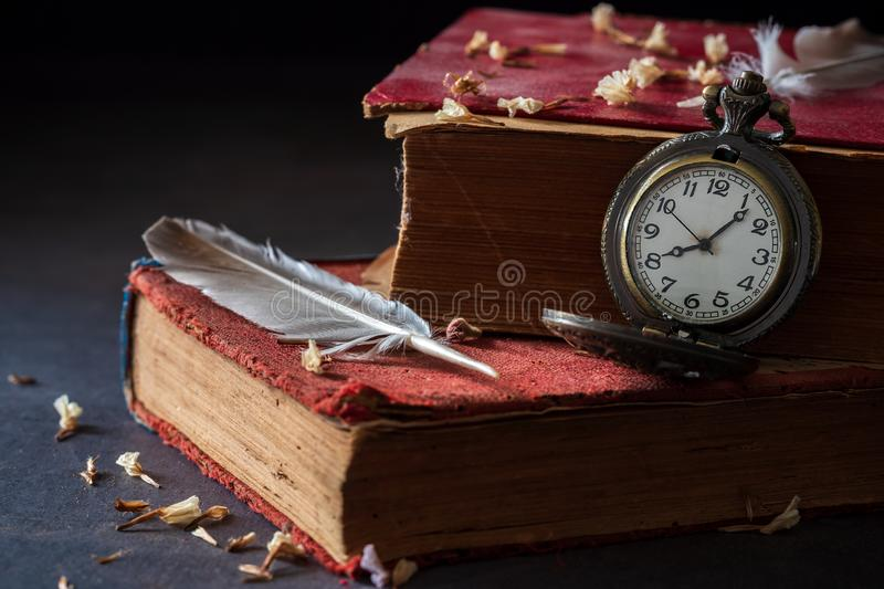 Winding pocket watch on old books with feathers and dried flower petals. Winding pocket watch on old books with feathers and dried flower petals on the marble royalty free stock photography