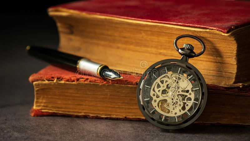 Winding pocket watch placed beside the old book and the pen on the book. Winding pocket watch placed beside the old book and the pen on the book in darkness and stock images