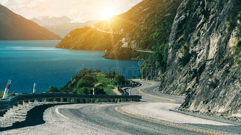 Winding road along mountain cliff and lake. Landscape in Queenstown, New Zealand South Island. Travel and road trip in summer stock images
