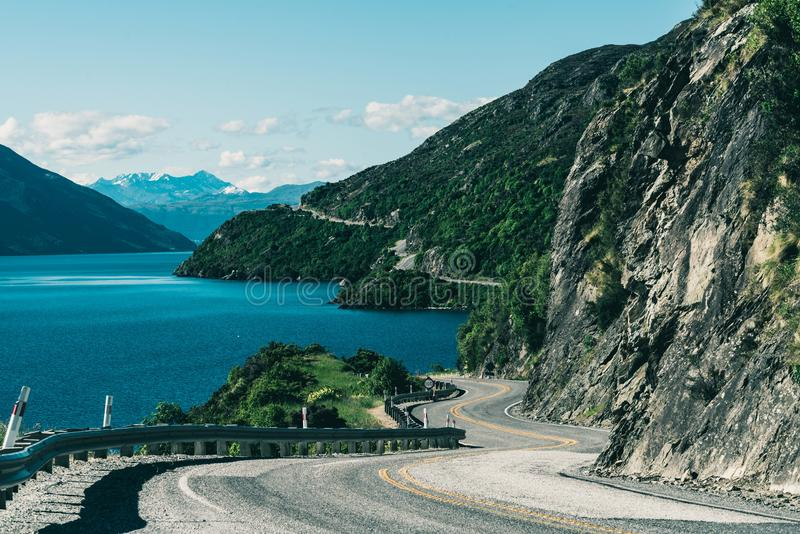 Winding road along mountain cliff and lake. Landscape in Queenstown, New Zealand South Island. Travel and road trip in summer stock photo