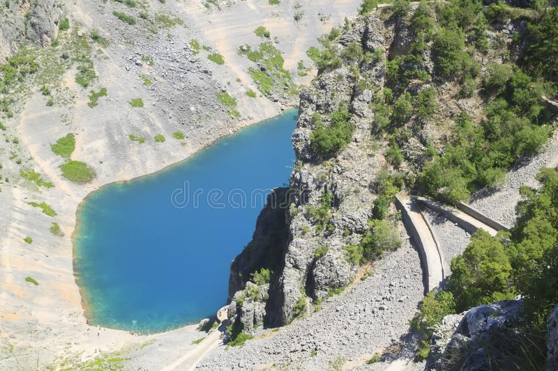 winding road down the steep slope of the mountain to the transparent deep blue karst lake in Imotski stock photo