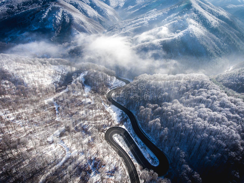 Winding road from the high mountain pass in Transylvania, Romania in the winter. Great road trip trough the dense woods. Aerial v. Iew royalty free stock image