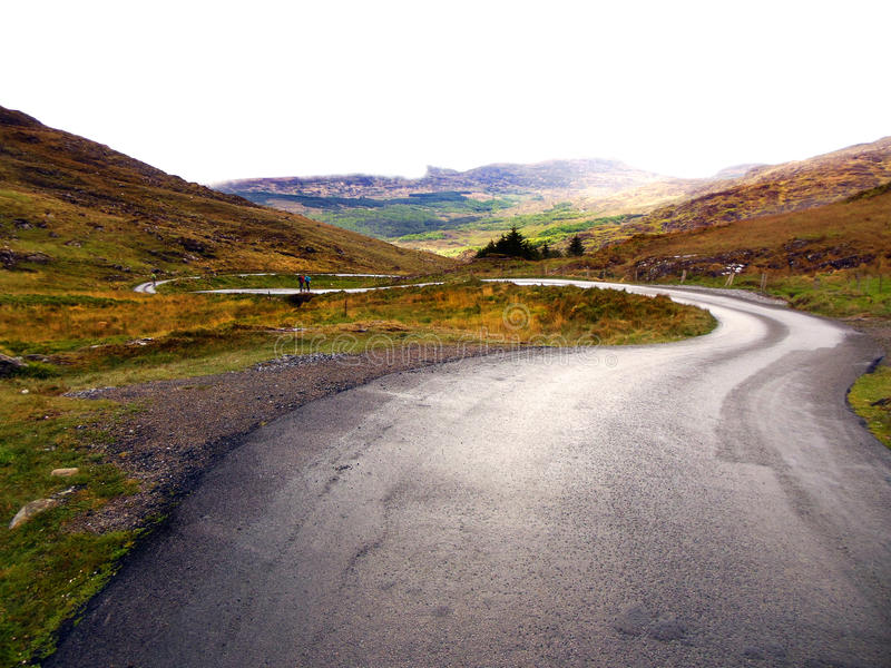 Winding Road in Ireland. Hiking after a rainstorm along a country road, winding through the Irish countryside through the Gap of Dunloe. The grass is lush and royalty free stock photography