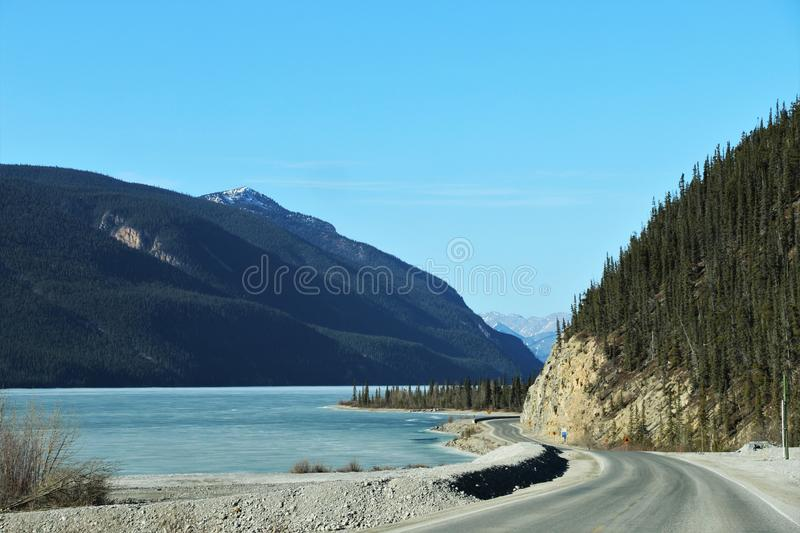 Mountain road between British Columbia, Canada and Alaska. Winding road by lake and snow capped mountains in distance in March 2019. Desolate road with no stock images