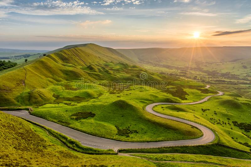 Long winding country road leading through rural countryside in the English Peak District with beautiful evening sunlight. stock images