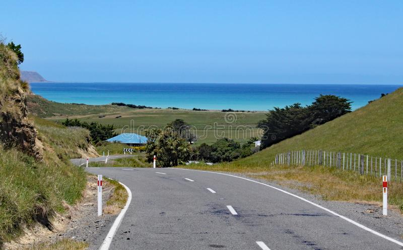 Winding road leads down to the sea in New Zealand royalty free stock photography