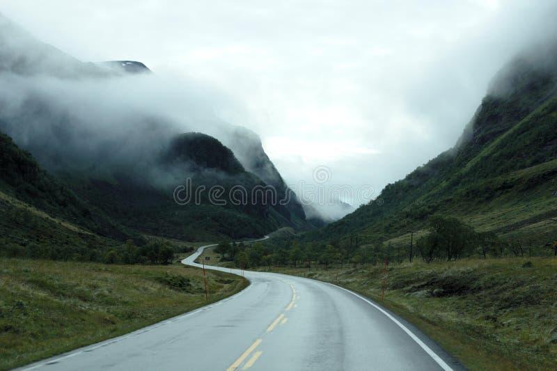 Winding road through mountain fog royalty free stock image
