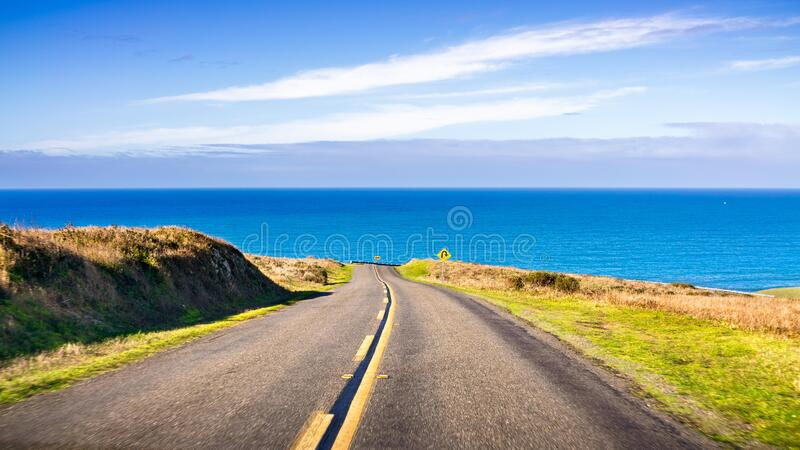 Winding road on the Pacific Ocean coastline on a clear sunny day, Point Reyes National Seashore, California royalty free stock photo