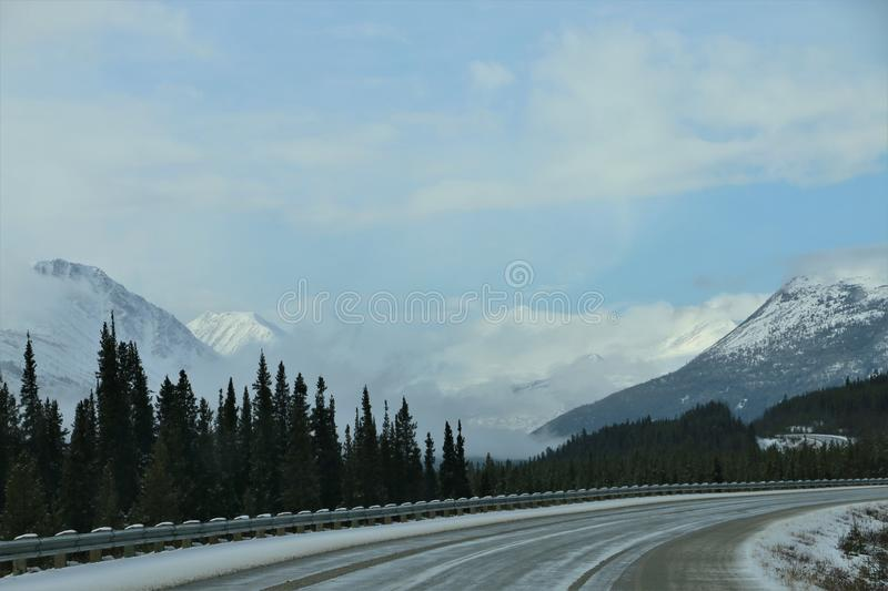 Snow covered mountain road between British Columbia, Canada and Alaska. Winding road in snow capped mountains in March 2019. Desolate road with no traffic stock image