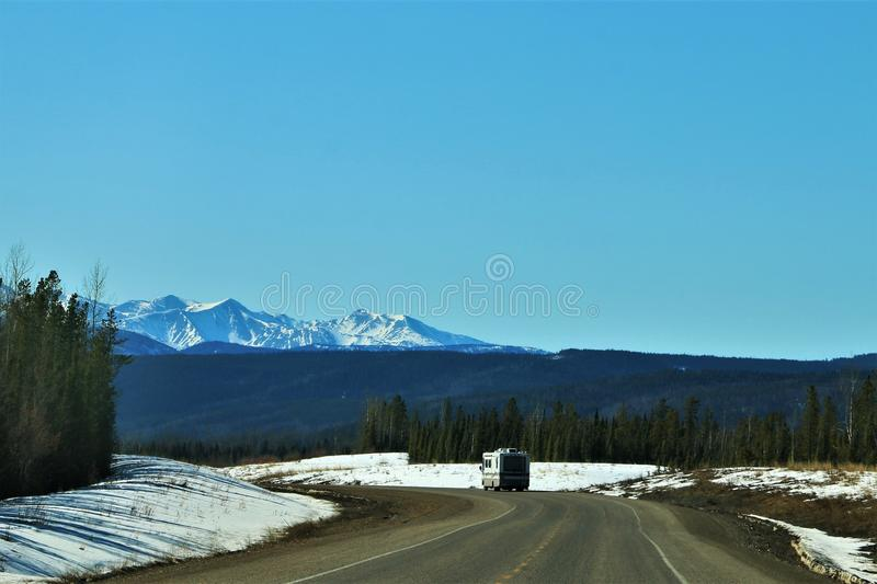 Snow covered mountain road between British Columbia, Canada and Alaska. Winding road in snow capped mountains in March 2019. Desolate road with single stock photos