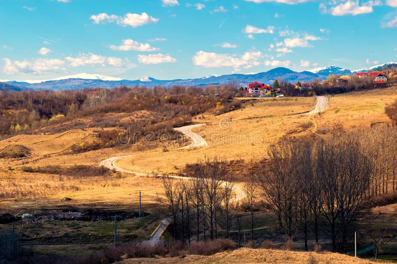 Winding road thru hills in early spring time and snow covered mountain peaks in the far background.  stock image