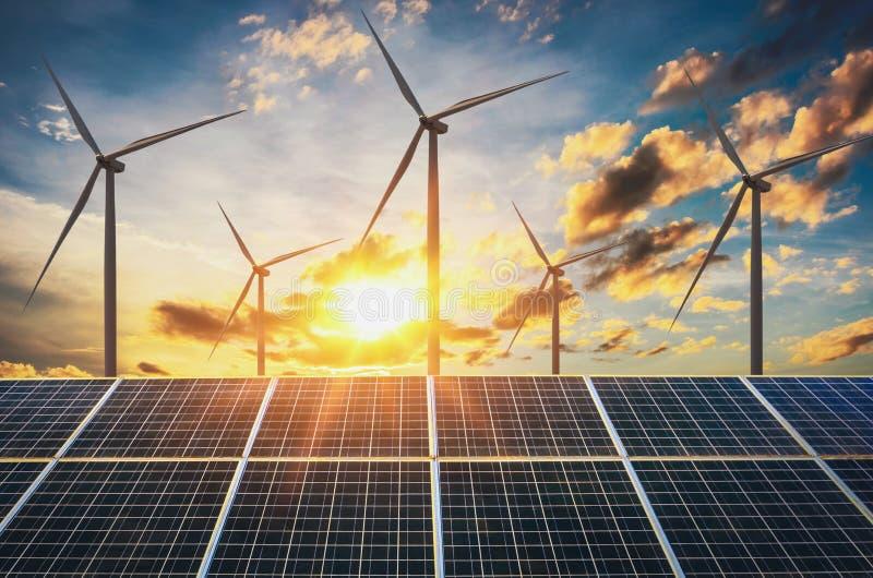 Windkraftanlage mit Sonnenkollektoren und Sonnenuntergang Konzept sauber lizenzfreie stockfotos