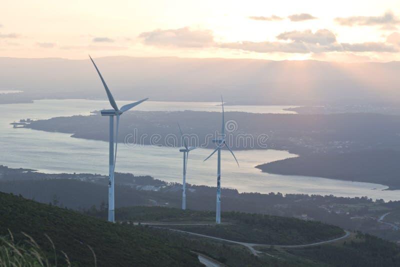 Windkraftanlagebauernhof mit Strahlen des Lichtes bei Sonnenuntergang lizenzfreie stockfotos
