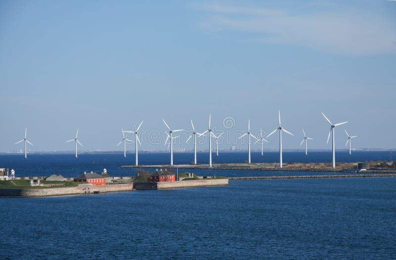 Windkraftanlagen bewirtschaften im Land und in Wasser, die alternative stützbare Energie schaffen Landscabe mit Raum des blauen  stockbild
