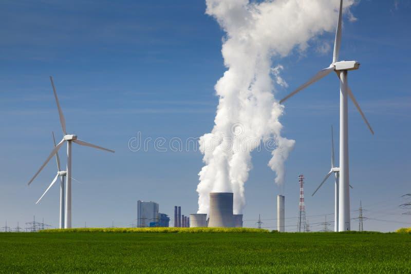 Windkraftanlagen gegen Kraftwerk-Luftverschmutzung der Kohle brennende stockfotografie