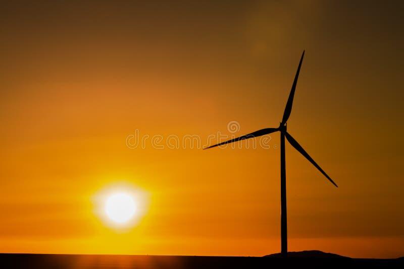 Windkraftanlagen silhouettieren bei dem Sonnenuntergang stockfoto
