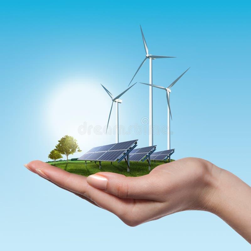 Windkraftanlagen und Sonnenkollektoren in der weiblichen Hand stockfotos