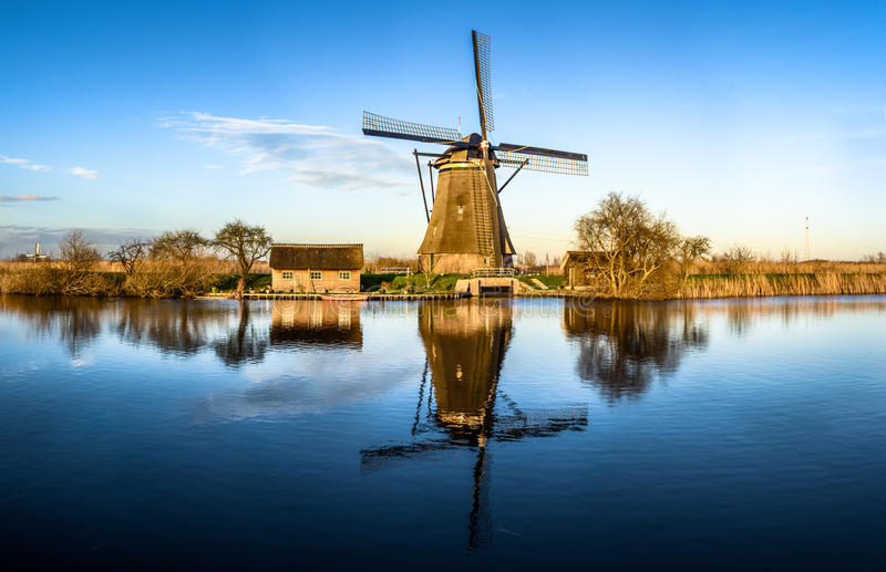 Windmühle, die im Wasser in den Niederlanden sich reflektiert stockbild