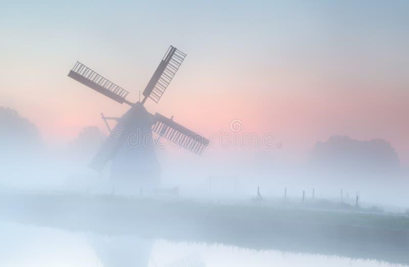 Windmühle im dichten Nebel bei Sommersonnenaufgang stockfoto