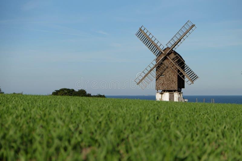 Windmühle nahe der Küste mit Ansicht zum Meer stockbilder