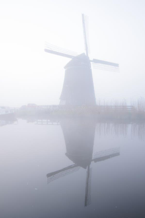 Windmühle und Reflexion im Nebel an der Dämmerung, die Niederlande lizenzfreies stockbild
