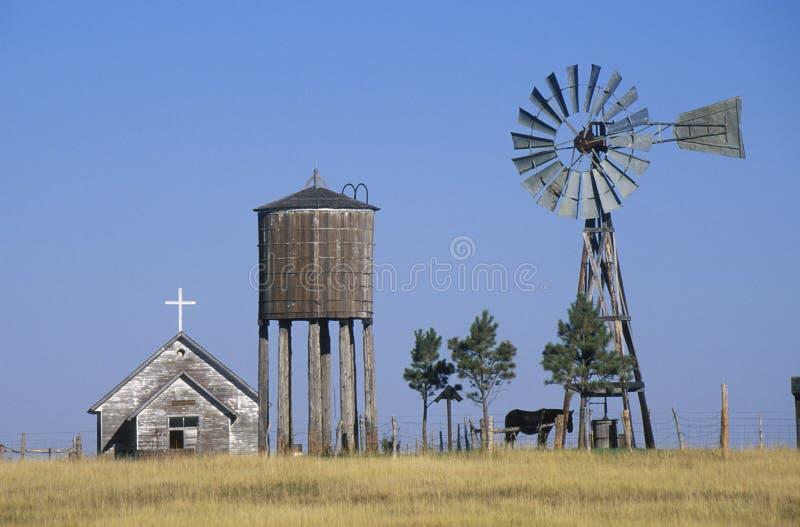 Windmühle und verlassene Graslandkirche, WY lizenzfreies stockbild