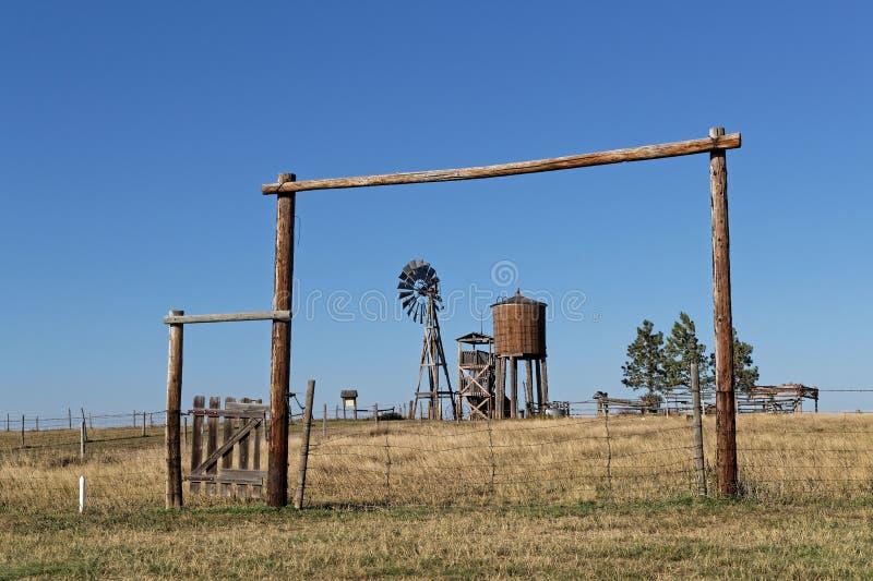 Windmühle und Zäune in einer Westlandschaft lizenzfreie stockfotos