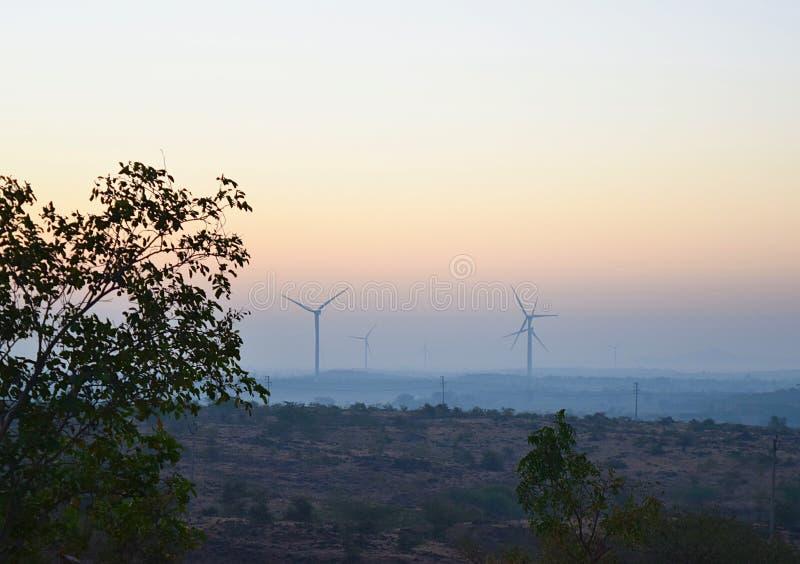 Windmühlen in einem Windpark auf Hügeln - eine indische Landschaft mit grüner Landschaft am frühen Morgen stockfotografie