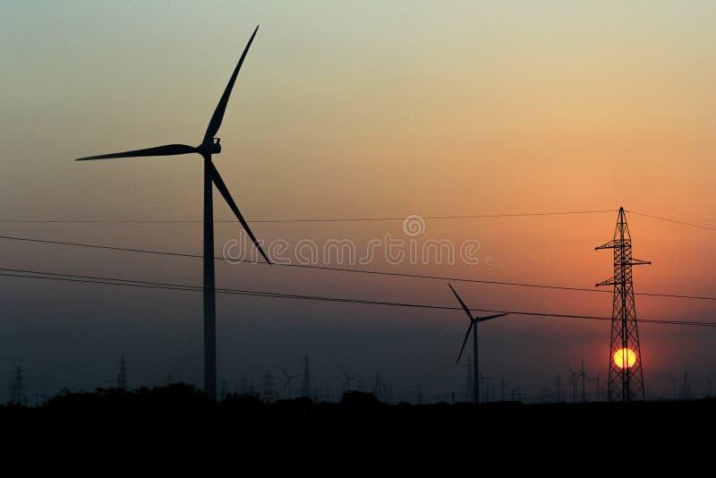 Windmühlen- und Sonnenuntergang- und Strompfosten stockbilder