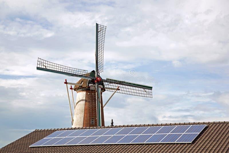 Windmil e comitati solari sul tetto fotografia stock libera da diritti