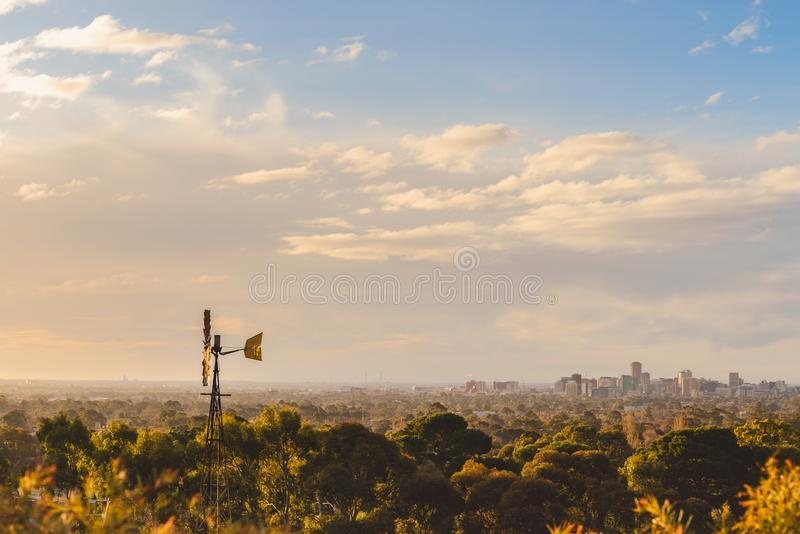 Windmill with Adelaide city skyline at sunset royalty free stock photos