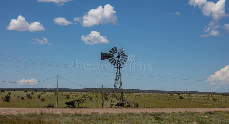 Windmill in an american countryside landscape. Cows in a pasture, sunny spring day, blue sky with clouds stock photo