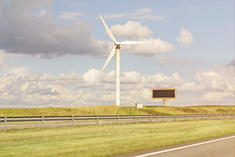 Windmill and billboardin in the field near the road royalty free stock images